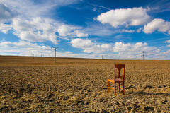 Old wooden chair on the empty field Royalty Free Stock Image
