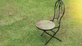 Old wooden chair on a green grass stock photography