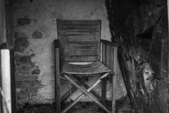 Old wooden chair isolated in dark and rough environment. Worn out and used wooden chair, standing lonely in a cold and dark room with an nature formed cliff wall stock images