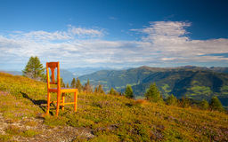Old wooden chair on the top in Gerlitzen Apls in Austria. Royalty Free Stock Photography