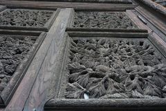 Old wooden chase carving of forestall motives on doors. Cones and needles of pins from low angle Stock Photography