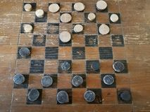 Old wooden checkerboard with black and white checkers royalty free stock images