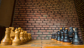 Old wooden chess. And brick wall on background Royalty Free Stock Photos