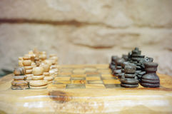 Old wooden chess pieces on a tree trunk board Stock Photo