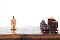 Old wooden Chessboard with lonely King versus opposing team, white background, copy space. Chess Game with lonely King versus full set of enemies, white stock images