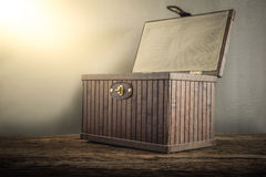Old wooden chest with open lit on wooden tabletop against grunge Stock Images