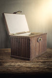 Old wooden chest with open lit on wooden tabletop against grunge Stock Photo