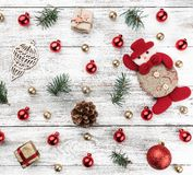 Old wooden Christmas background. Red and gold Baubles. Fir branches and cones. Xmas items. Top view. Square card.  royalty free stock image