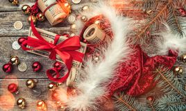 Old wooden Christmas background, Santa Claus, baubles and money coins and Xmas items. Top view. Effect of light blips.  stock photo
