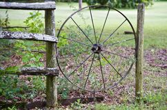 Chuck Wagon Wheel Wooden. Old Wooden Chuck Wagon wheel that has been built into a wooden hand constructed fence Royalty Free Stock Image