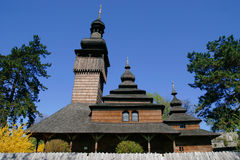 Old wooden church. Old wooden brown church surrounded by trees and bloom bushes Royalty Free Stock Photography