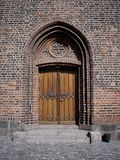 Old wooden church door. A wooden church door with cross and bricks and cobble stones Royalty Free Stock Image
