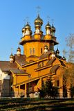 Old wooden Church with gold domes on blue sky background at sunset. Russia, Belgorod. Vertical view Royalty Free Stock Images