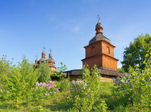 Old wooden church and lilac trees Stock Images