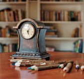 Old wooden clock and colored pencils royalty free stock images