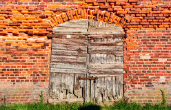 Old wooden closed shutters on the wall from red bricks Stock Photography