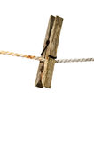 Old wooden clothes peg. On a rope royalty free stock photo