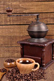 Old wooden coffee grinder and roasted coffee beans on a wooden table . Fresh hot coffee in Cup Stock Photos