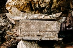 Old wooden coffin with skulls and bones nearby on a rock. Hanging coffins, graves. Traditional burials site, cemetery Kete Kesu in Stock Image