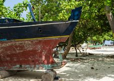 Old wooden colorful boat on the white sand of the tropical island. Maldives, wild paradise. Maldives - November, 2017: close-up: an old wooden boat standing on a Stock Images