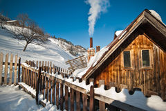 Old wooden cottage with hill covered by snow in background. Bright cold winter day in the mountains landscape.Carpathian mountains Royalty Free Stock Photo