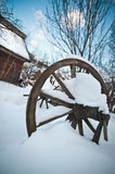Old wooden cottage and wooden Romanian wheel covered by snow. Cold winter day at countryside. Traditional Carpathian mountains Royalty Free Stock Images