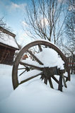 Old wooden cottage and wooden Romanian wheel covered by snow. Cold winter day at countryside. Traditional Carpathian mountains Royalty Free Stock Photography