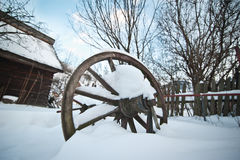 Old wooden cottage and wooden Romanian wheel covered by snow. Cold winter day at countryside. Traditional Carpathian mountains Stock Image