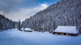 Old wooden cottages in winter mountains Stock Photos