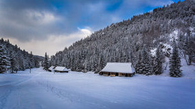 Old wooden cottages in winter mountains Stock Images