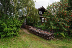 Old wooden country house with stack of boards Royalty Free Stock Photos