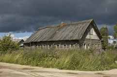 Old wooden country house before storm. Old broken wooden house in russian village near Kargopol, before storm Stock Image