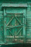 Old wooden country window with closed shutters painted green Stock Photography