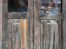 An old wooden cracked door with two panes at the top, a wall of the neighboring house is reflected in the glass. Royalty Free Stock Photos