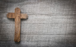 Old and wooden cross on a background. Old wooden cross on a old wooden background with copy space for a condolence text Royalty Free Stock Photos