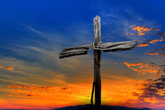 Old wooden cross over dramatic sunset. Christian cross over blue and yellow sunset background stock images