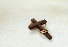 Old wooden cross with two golden rings. On white wedding lace Royalty Free Stock Photography