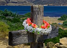 Wooden cross with wreath in background of coast Stock Photography