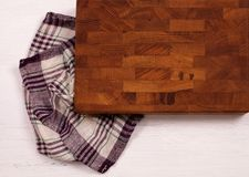 Old wooden cutting board with kitchen towel on white wooden table. stock photos