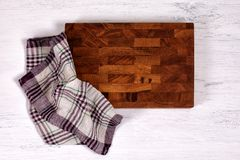 Old wooden cutting board with kitchen towel on white wooden table. royalty free stock photo