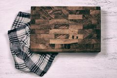 Old wooden cutting board with kitchen towel on white wooden table. royalty free stock photography