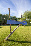 Old wooden decayed empty sign. Blue sign made of wood with green grass and blue sky in background Royalty Free Stock Photos
