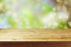 Old wooden deck table with spring bokeh background. Ready for product display montage. Royalty Free Stock Images