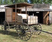 Old wooden delivery wagon. Historic or old wooden delivery wagon or carriage with old blacksmith shop in background Stock Photography