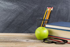 Old wooden desktop with green apple and reading materials Royalty Free Stock Image