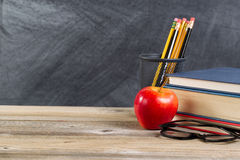 Old wooden desktop with reading materials and blackboard Royalty Free Stock Photography