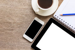 Old wooden desktop with tablet, smartphone, coffee cup, notebook and pencil, Top view stock photo