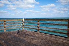 Old wooden dock with fishing rod. Balanced aainst the railing overlooking a tranquil sea in Florida, USA Royalty Free Stock Photos