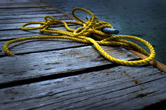 Old Wooden Dock by Water Yellow Rope Royalty Free Stock Photography