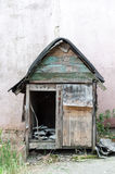 Old wooden dog house by the wall Royalty Free Stock Photography